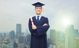 Lächelnder erwachsener Student in der Doktorhut mit Diplom stockbild