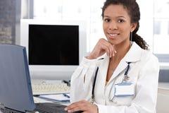Lächelnder ethnischer Doktor mit Laptop-Computer Stockfoto