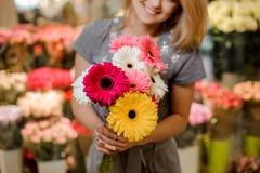 Lächelnder Florist in einem grauen Kleid, das einen schönen bunten Blumenstrauß von Blumen hält Lizenzfreies Stockfoto