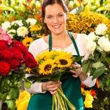 Lächelnder Floristenfrauenblumenstrauß-Sonnenblume-Blumenladen lizenzfreie stockfotos