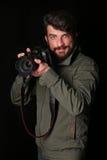 Lächelnder Fotograf mit einer Kamera Abschluss oben Schwarzer Hintergrund Stockbilder