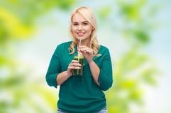 Lächelnder Frau trinkender Gemüsesaft oder Smoothie Stockfotografie