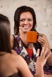 Lächelnder Frauen-trinkender Kaffee mit Freund Stockfotos