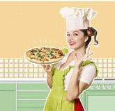Lächelnder Frauenchef, der Pizza in der Küchencollage hält Stockbilder