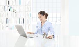 Lächelnder Frauengebrauch des Hauptkonzeptes der Computer und das darstellen Haus MO Stockfotografie