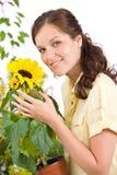 Lächelnder Frauenholding-Blumenpotentiometer mit Sonnenblume Stockbilder