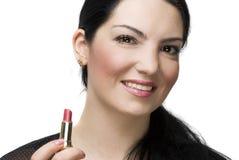 Lächelnder Frauenholdinglippenstift Stockfotos