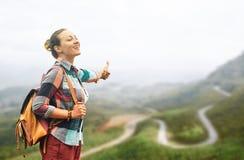 Lächelnder Frauenreisender, der Freiheit mit der hohen Hand auf Straße genießt lizenzfreie stockbilder