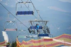 Lächelnder Frauenskifahrer im blauen Skianzug, der bis zur Spitze des Berges auf einen Kabelskiaufzug mit Himmeln fährt Stockfoto
