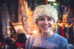 Lächelnder Frauentourist, der auf traditionellem Balkan-Hut auf lokalem Andenkenmarkt während ihrer Reisefeiertage versucht Stockbilder