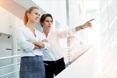 Lächelnder Frauenunternehmer, der mit den gekreuzten Armen, während ihr, steht Untergebener etwas durch das Bürofenster zeigt, Lizenzfreie Stockbilder