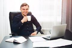 Lächelnder Freiberufler, der an Projekt in seinem Kabinett arbeitet Trinkender Kaffee Stockfoto