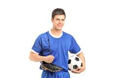 Lächelnder Fußballspieler im Sport tragen das Anhalten der Schuhe und des Fußes eines Fußballs Stockbild