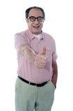 Lächelnder gealterter männlicher gestikulierender Thumbs-up lizenzfreies stockfoto