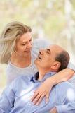 Lächelnder gealterter Mann und Frau, die sich umarmen Stockfotografie