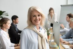 Lächelnder gealterter Unternehmensleiter oder Teamleiter, die Kamera betrachten stockbild
