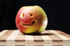 Lächelnder gegenübergestellter Apfel auf hölzernem Vorstand Lizenzfreie Stockbilder