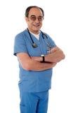 Lächelnder gereifter Doktor, der mit den gefalteten Armen aufwirft stockfoto
