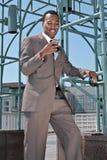 Lächelnder Geschäftsmann auf Handy Stockfotografie