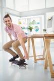 Lächelnder Geschäftsmann beim Skateboard fahren Lizenzfreie Stockbilder