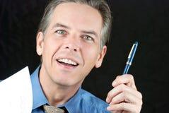 Lächelnder Geschäftsmann bietet Feder an Stockfoto
