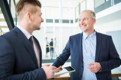 Lächelnder Geschäftsmann Communicating With Colleague im Büro lizenzfreie stockbilder