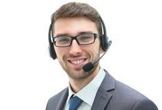 Lächelnder Geschäftsmann, der auf Kopfhörer gegen ein weißes backgroun spricht Lizenzfreies Stockfoto