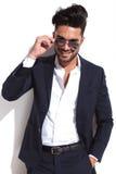 Lächelnder Geschäftsmann, der auf seine Sonnenbrille sich setzt Stockbild