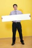 Lächelnder Geschäftsmann, der breite unbelegte weiße Karte anhält lizenzfreies stockbild