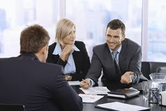 Geschäftsmann, der bei der Sitzung lächelt Stockfotografie