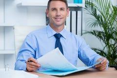 Lächelnder Geschäftsmann, der ein contrat liest, bevor es unterzeichnet wird Stockbilder