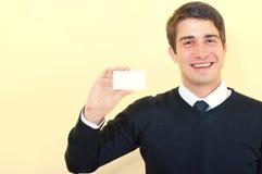 Lächelnder Geschäftsmann, der eine unbelegte Visitenkarte zeigt stockfotografie