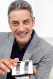 Lächelnder Geschäftsmann, der eine Visitenkartehalterung anhält Stockfotografie