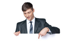 Lächelnder Geschäftsmann, der etwas auf leerem Plakat zeigt. Stockfotografie