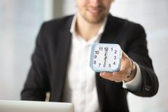 Lächelnder Geschäftsmann, der in der Hand kleine Uhr hält Lizenzfreies Stockbild