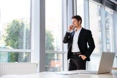 Lächelnder Geschäftsmann, der am Handy im Büro steht und spricht Lizenzfreie Stockfotos