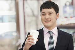 Lächelnder Geschäftsmann, der Kaffeetasse hält Stockfotos