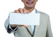 Lächelnder Geschäftsmann, der leeres Papier zeigt Lizenzfreies Stockfoto