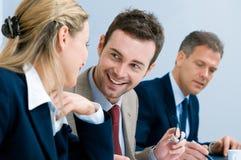 Lächelnder Geschäftsmann, der mit Kollegen spricht Stockbild