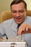 Lächelnder Geschäftsmann, der Schach spielt Stockfoto