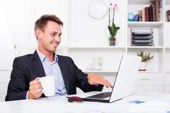 Lächelnder Geschäftsmann, der Schale mit Kaffee hält Lizenzfreie Stockbilder