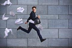 Lächelnder Geschäftsmann, der schnell mit Aktenkoffer an der Stadt läuft Lizenzfreie Stockfotos