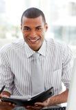 Lächelnder Geschäftsmann, der seine Tagesordnung konsultiert Stockfotos