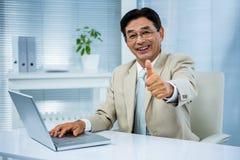 Lächelnder Geschäftsmann, der sich Daumen zeigt Lizenzfreie Stockfotos