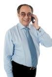 Lächelnder Geschäftsmann, der Telefonaufruf bedient stockfotos