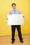 Lächelnder Geschäftsmann, der unbelegte weiße Karte anhält lizenzfreies stockfoto