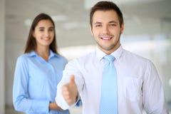 Lächelnder Geschäftsmann im Büro ist zum Rütteln von Händen bereit Stockfotografie