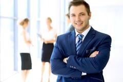Lächelnder Geschäftsmann im Büro mit Kollegen im Hintergrund Stockfotografie