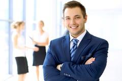 Lächelnder Geschäftsmann im Büro mit Kollegen im Hintergrund Stockfoto
