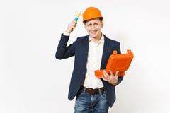 Lächelnder Geschäftsmann im dunklen Anzug, schützender Hardhatholdingfall mit Instrumenten oder Werkzeugkasten und an sich schlag lizenzfreie stockfotografie